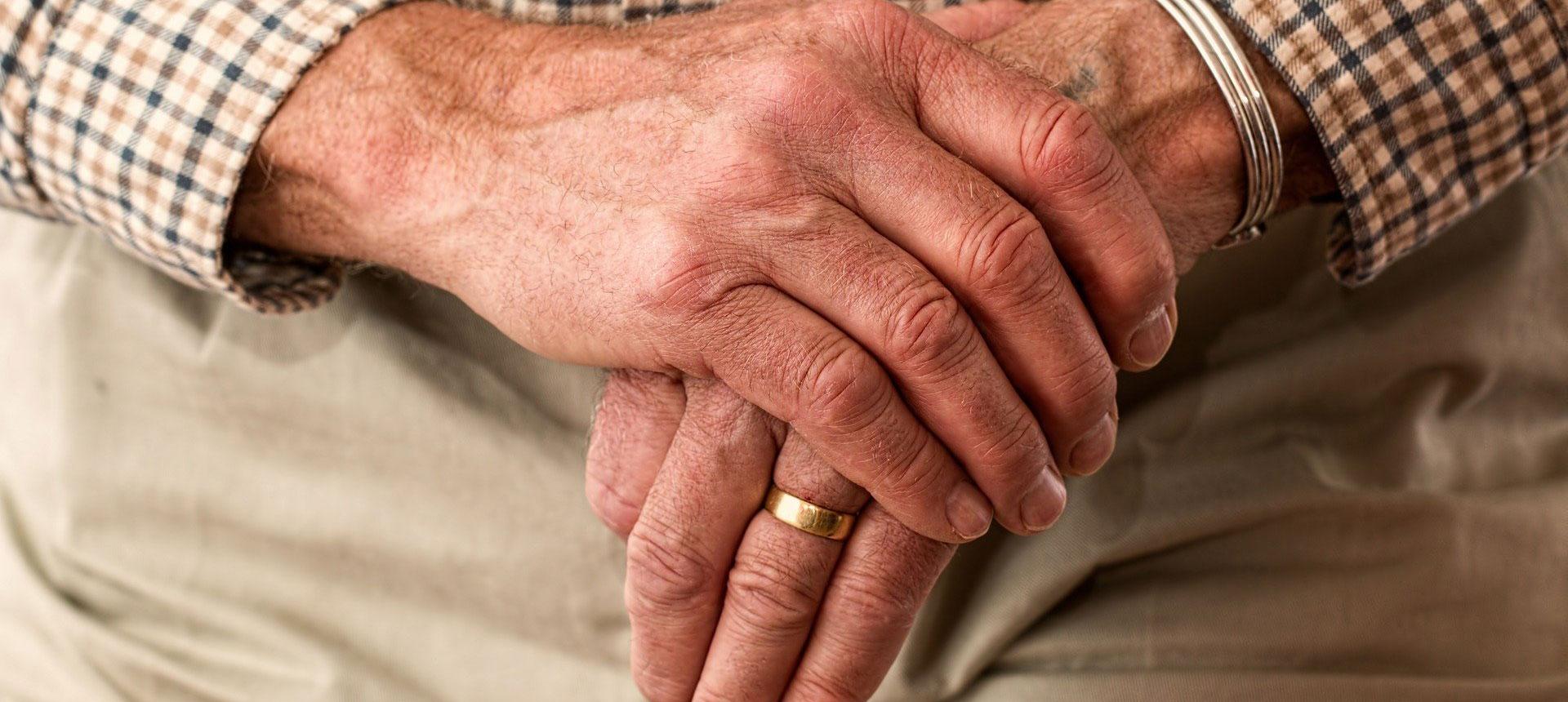 Elderly hands holding a cane.
