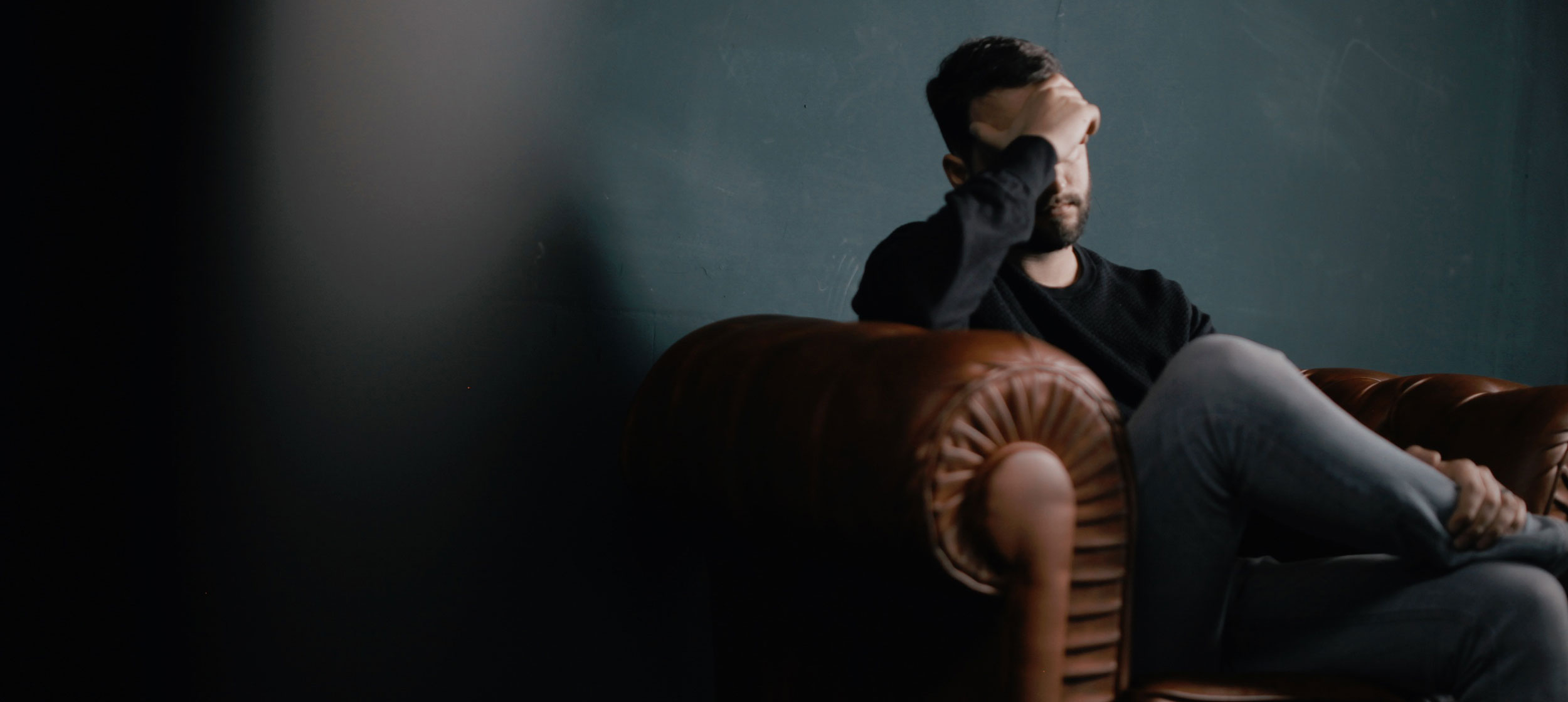 man sitting on sofa against wall holding his head